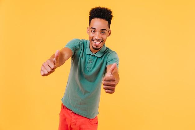 Ekstatyczny afrykański mężczyzna chłodzi. portret pewny siebie czarny model męski w zielonej koszulce.