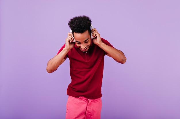 Ekstatyczny czarny młody człowiek dotyka jego słuchawek i patrzy w dół. wewnątrz zdjęcie modela jocunda w czerwonym stroju.
