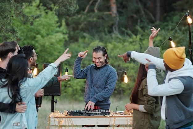 Ekstatyczny młody człowiek w kurtce i słuchawkach grający muzykę i tańczący z tłumem przyjaciół w letni weekend w naturalnym środowisku