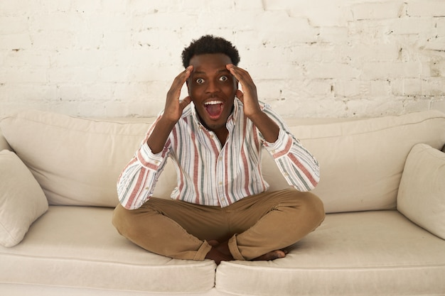 Ekstatyczny podekscytowany młody afrykański mężczyzna siedzi w salonie trzymając ręce na głowie, wykrzykując wow, omg, będąc pod wrażeniem