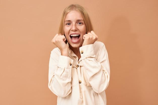Ekstatyczny, szczęśliwy, młody zwycięzca loterii z dopingiem aparatów ortodontycznych, świętujący sukces