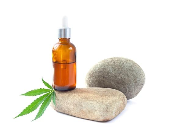Ekstrakt olejowy z marihuany w butelce z zakraplaczem obok liścia konopi
