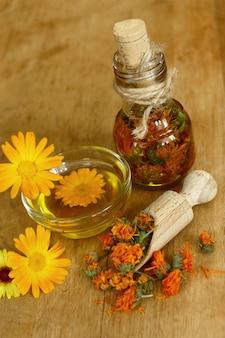 Ekstrakt z nagietka. rośliny lecznicze butelki i suszone płatki nagietka lekarskiego z macerowanym olejem na drewnianym stole.