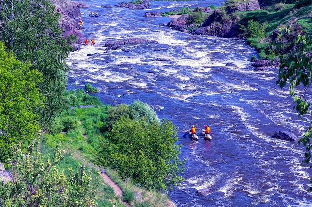 Ekstremalna rafting. grupa ludzi (zespół) w kajakach ćwiczy pokonywanie progów wodnych. kayaker brodzik na rzece górskiej. koncepcja kajakarstwa.