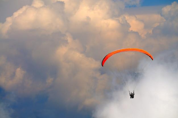 Ekstremalna rekreacja, spadochroniarz leci nad górami i skałami. białe chmury na niebie