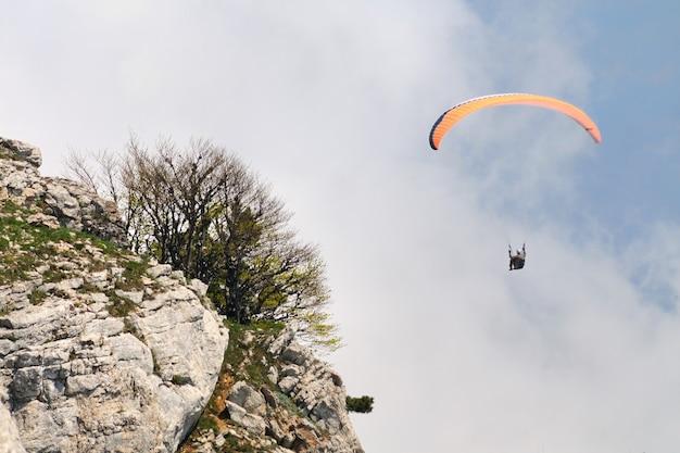 Ekstremalna rekreacja, spadochroniarz leci nad górami i skałami.