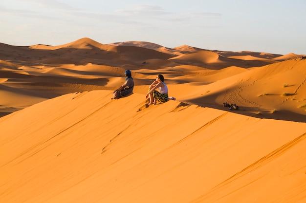 Ekstremalne długie ujęcie dwóch osób siedzących na szczycie wydmy