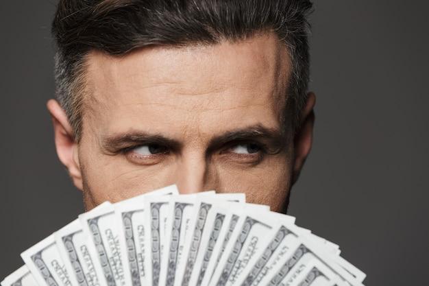 Ekstremalne zdjęcie z bliska pewnego siebie mężczyzny w wieku 30 lat trzymającego na twarzy fanem banknotów dolarowych i surowym spojrzeniem, odizolowane na szarej ścianie
