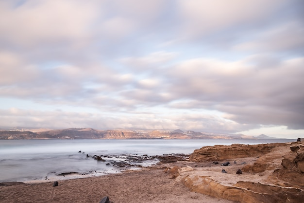 El confital plaża przy wschodem słońca w granie canaria, wyspy kanaryjska, hiszpania. wybrzeże wulkaniczny krajobraz.