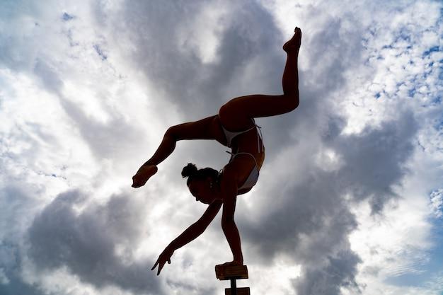 Elastyczna artystka cyrkowa utrzymuje równowagę jedną ręką, siłą woli i potencjalną koncepcją