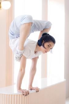 Elastyczna dziewczyna ćwiczy rozciąganie i stanie na rękach w domu koncepcja czasu kwarantanny podczas izolacji