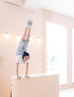 Elastyczna dziewczyna ćwiczy rozciąganie i stanie na rękach w domu koncepcja kreatywności indywidualności