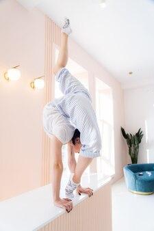 Elastyczna dziewczyna ćwiczy rozciąganie i stanie na rękach w domu koncepcja zdrowego stylu życia i jogi
