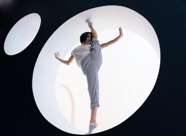 Elastyczna dziewczyna robi rozciąganie w studio koncepcji motywacji siły woli i zdrowego stylu życia