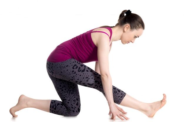 Elastyczna dziewczyna rozciągania mięśni w prawej nodze