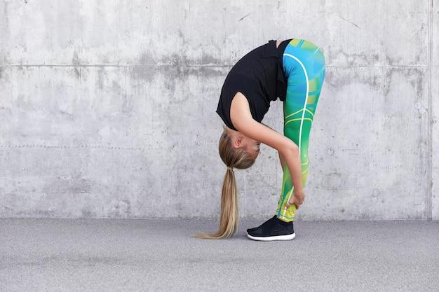 Elastyczna dziewczyna sportowa przybiera różne pozy podczas ćwiczeń sportowych