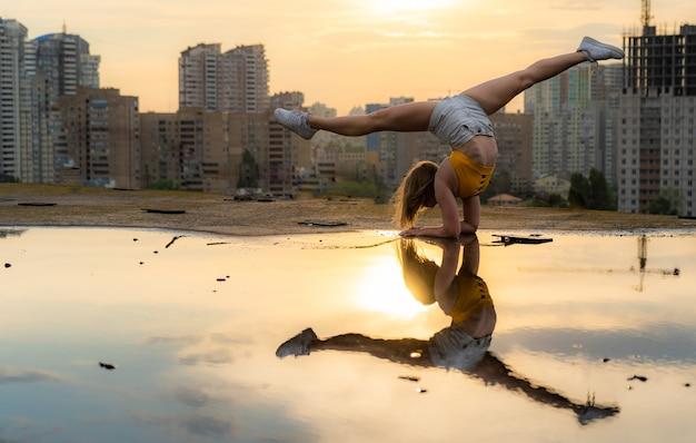 Elastyczna gimnastyczka robi handstand i kalistenika z odbiciem w wodzie na pejzaż miejski
