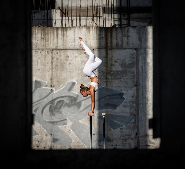 Elastyczna i sprawna dziewczyna stojąca na rękach utrzymująca równowagę w opuszczonym budynku
