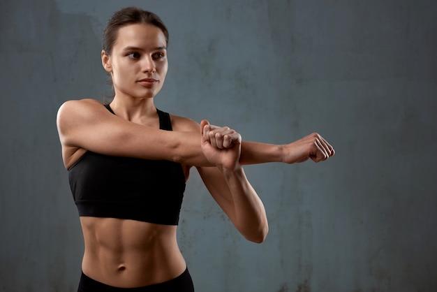 Elastyczna kobieta fitness rozciągająca ramię przed treningiem