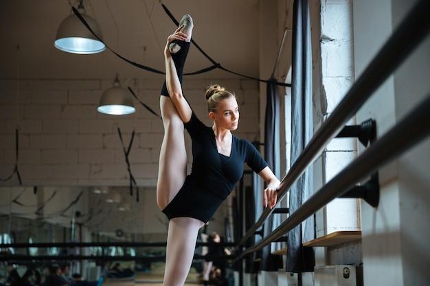 Elastyczna kobieta robi ćwiczenia rozciągające na zajęciach baletowych