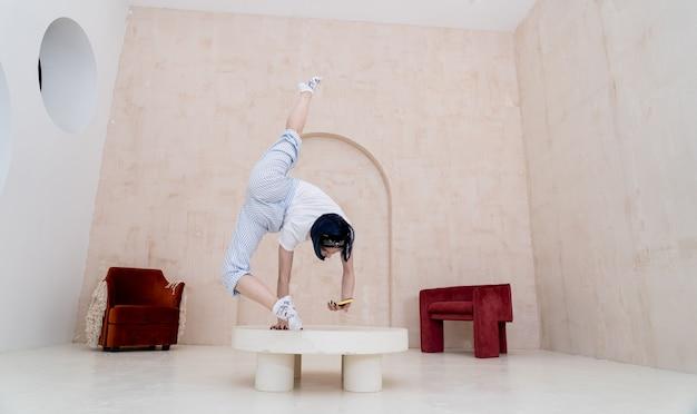 Elastyczna kobieta utrzymuje równowagę z jednej strony, podczas gdy smartfon w domu koncepcja jogi i indywidualności