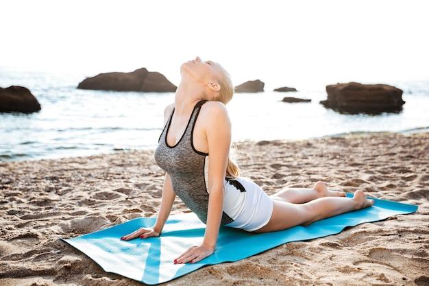 Elastyczna młoda kobieta robi ćwiczenia rozciągające jogi na plaży