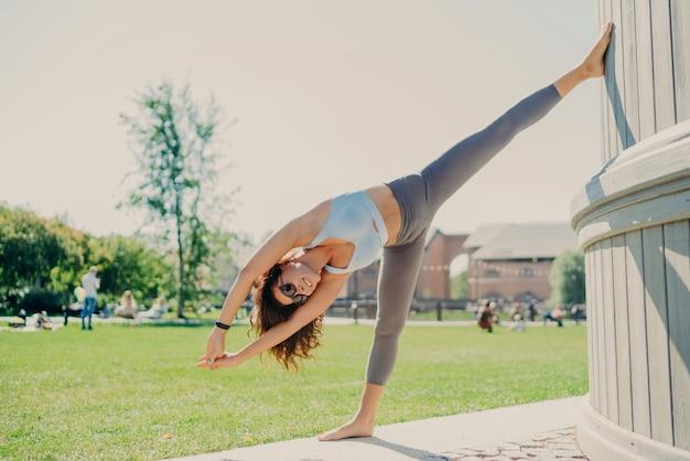 Elastyczna, szczupła kobieta wykonuje ćwiczenia rozciągające na świeżym powietrzu w dobrej kondycji fizycznej ubrana w krótki top i legginsy stoi na jednej nodze z uniesionymi rękoma rozgrzewa się przed treningiem cardio