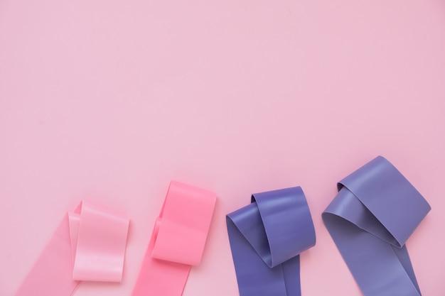 Elastyczna taśma fitness, elastyczne przedłużki w różnych kolorach do uprawiania sportu, na różowym tle. trend fitness.