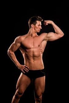 Elastyczne ramię kulturysty z bicepsem, tricepsem. człowiek pokazuje muskularne ciało, mięśnie. sportowiec z nagim torsem, sześciopak, ab na czarnym tle. sport, kulturystyka, fitness. pojęcie zdrowego stylu życia.