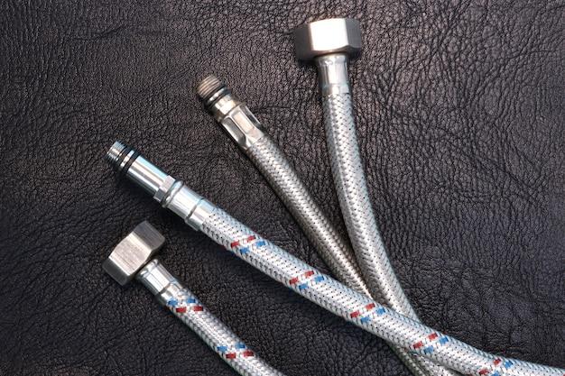 Elastyczne węże wodne w metalowej wylewce do podłączenia sprzętu hydraulicznego. czarne skórzane teksturowane tło. skopiuj miejsce na tekst.