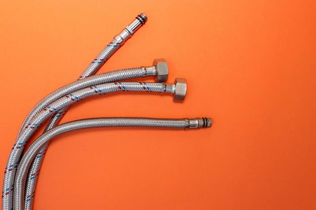 Elastyczne węże wodne w metalowej wylewce do podłączenia sprzętu hydraulicznego. jasne pomarańczowe tło gradientowe. skopiuj miejsce na tekst.