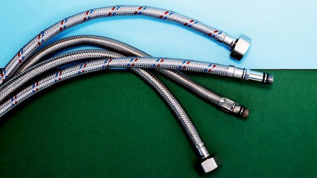 Elastyczne węże wodne w metalowej wylewce do podłączenia sprzętu hydraulicznego. zielone i niebieskie tło z naturalnymi cieniami. skopiuj miejsce na tekst.