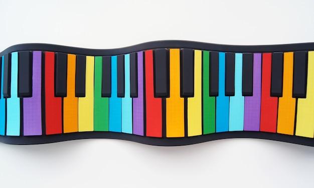 Elastyczne, wielokolorowe pianino dla dzieci. widok z góry na białym tle na białej ścianie
