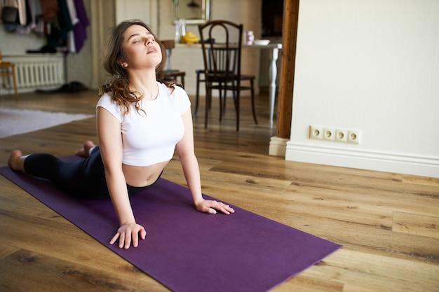 Elastycznie dopasowana młoda kobieta w stroju sportowym, rano ćwiczy sekwencję jogi na powitanie słońca, pochyla się do tyłu na macie, robi z psem twarzą do góry, ma zamknięte oczy i głęboko oddycha. zdrowe ciało i umysł