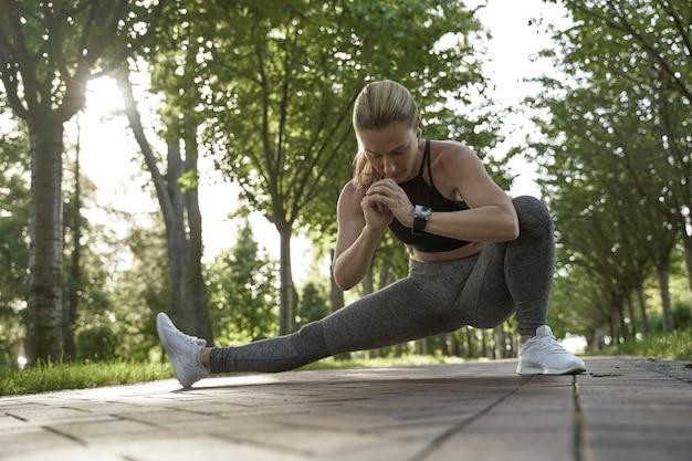 Elastyczność na całej długości pięknej fitnessowej kobiety w sportowej odzieży rozciągającej nogi podczas