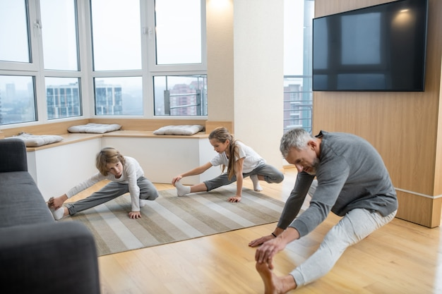 Elastyczność. ojciec i jego dzieci wspólnie uprawiają jogę w domu i głęboko się rozciągają