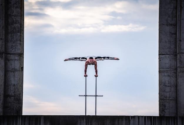 Elastyczny męski cyrk artysta utrzymuje równowagę na rękach w betonowej konstrukcji na tle nieba z odbiciem w wodzie