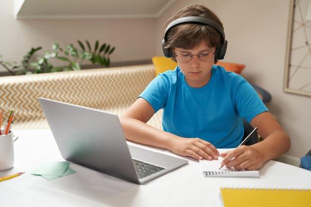 Elearning inteligentny mały chłopiec w słuchawkach za pomocą laptopa podczas nauki online, siedząc przy stole w