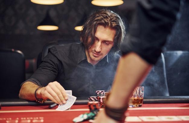 Eleganccy młodzi ludzie siedzą przy stole i grają w pokera w kasynie z dymem w powietrzu