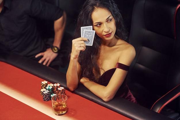 Eleganccy młodzi ludzie siedzą przy stole i grają w pokera w kasynie