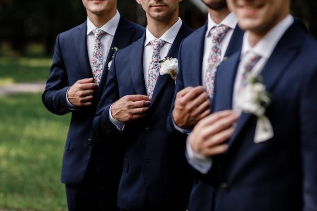 Eleganccy panowie młodzi z eleganckim krawatem w kwiaty. białe kwiaty w dziurce, mężczyźni pana młodego ubrani są w ciemny garnitur. dzień ślubu. strój dnia.