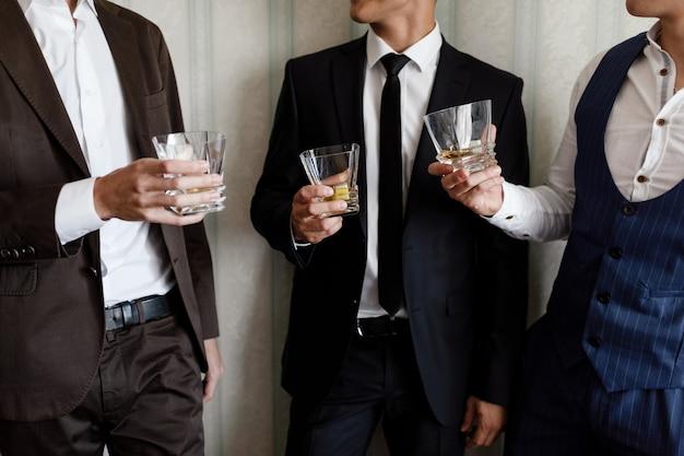 Eleganccy przyjaciół biznesmeni wznosi toast z szkłami whisky indoors w kostiumach, zbliżenie. poranek pana młodego