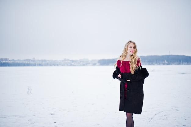 Elegancja blondynka w futrze i czerwona suknia wieczorowa pozowanie w zimowy śnieżny dzień.