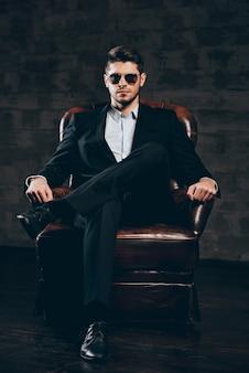 Elegancja i męskość. młody przystojny mężczyzna w garniturze i okularach przeciwsłonecznych, trzymając rękę na brodzie i patrząc na kamerę siedząc w skórzanym fotelu na ciemnoszarym tle