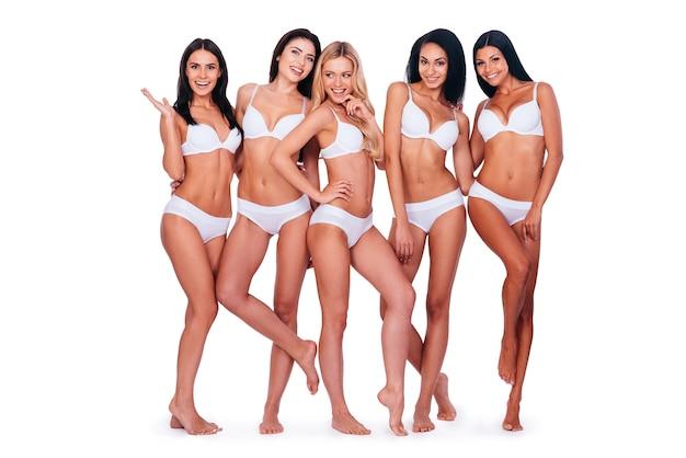 Elegancja i piękno. pełna długość pięciu pięknych młodych kobiet w bieliźnie pozujących i uśmiechających się, łącząc się ze sobą i stojąc na białym tle