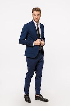 Elegancja, pewność siebie i koncepcja biznesowa. dobrze wyglądający młody brodaty blond biznesmen w garniturze i krawacie, naprawiający kurtkę, wyglądający poważnie i pewny siebie, zdeterminowany, robi dobry interes