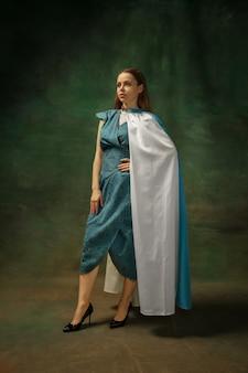 Elegancja pozowanie. portret średniowiecznej młodej kobiety w niebieskiej odzieży vintage na ciemnym tle. modelka jako księżna, osoba królewska. pojęcie porównania epok, nowoczesności, mody, piękna.