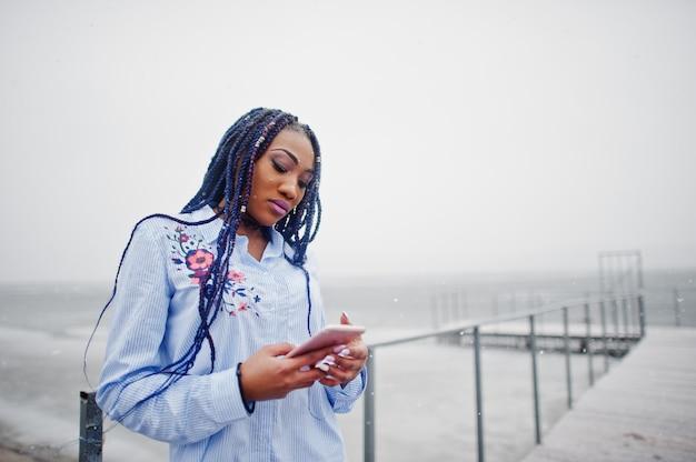 Elegancka amerykanin afrykańskiego pochodzenia dziewczyna trzyma telefon komórkowego pod ręką z strachami, plenerowy na molu przeciw zamarzniętemu jezioru przy śnieżną pogodą.
