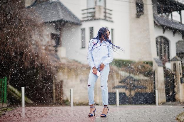 Elegancka amerykanin afrykańskiego pochodzenia dziewczyna trzyma telefon komórkowy pod ręką z strachami, plenerowa śnieżna pogoda.