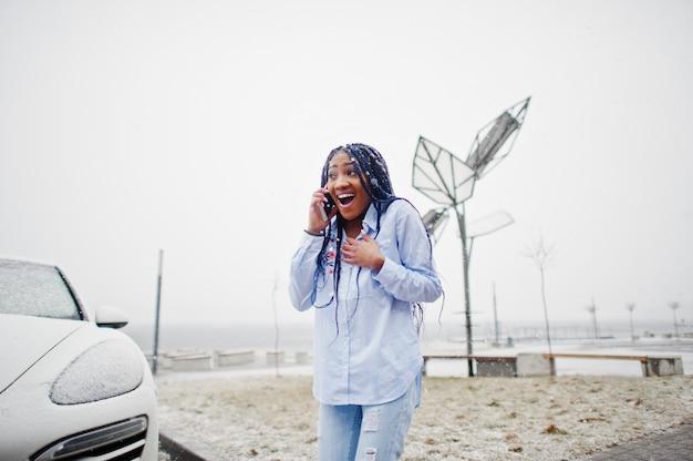 Elegancka amerykanin afrykańskiego pochodzenia dziewczyna trzyma telefon komórkowy pod ręką z strachami, plenerowymi przeciw białemu samochodowi i bateriami słonecznymi przy śnieżną pogodą.